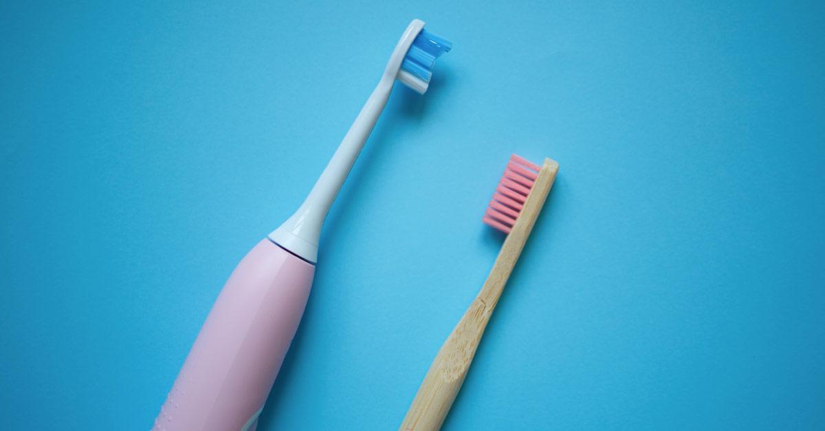 Cepillo de dientes eléctrico rosa y blanco de perfil frente a un cepillo de dientes manual de madera con las cerdas de color rosa. Esta imagen se utiliza para ilustrar una entrada sobre cómo elegir un buen cepillo de dientes.