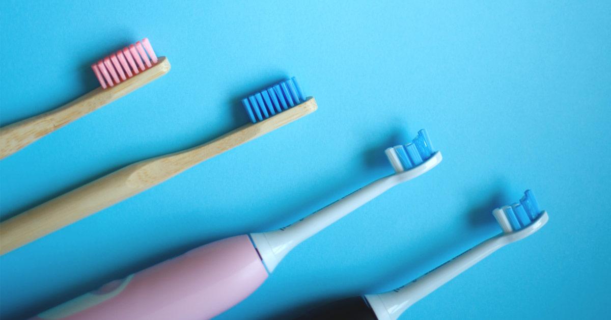 Cuatro cepillos de dientes dispuestos en diagonales. Arriba, se sitúa uno manual de madera con las cerdas rosas. Debajo de este, uno de madera manual con las cerdas azules. Debajo, uno eléctrico blanco y rosa. El último es eléctrico y negro y blanco.