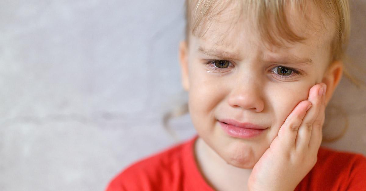 Peque llorando con una mano en la mejilla. Esta imagen se utiliza para ilustrar una entrada sobre qué hacer si un niño lleva un golpe en los dientes.