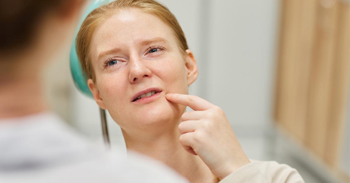 Mujer explicándole a la dentista qué pieza dental le duele.