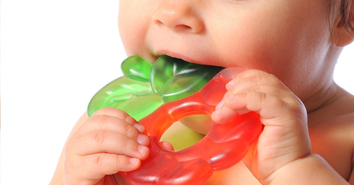 Primer plano de la boca de un bebé mordiendo un mordedor que sostiene con las manos.