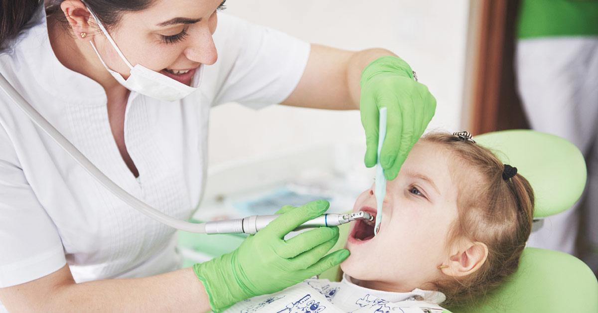 Dentista sonriendo haciendo algo en la boca de una niña.