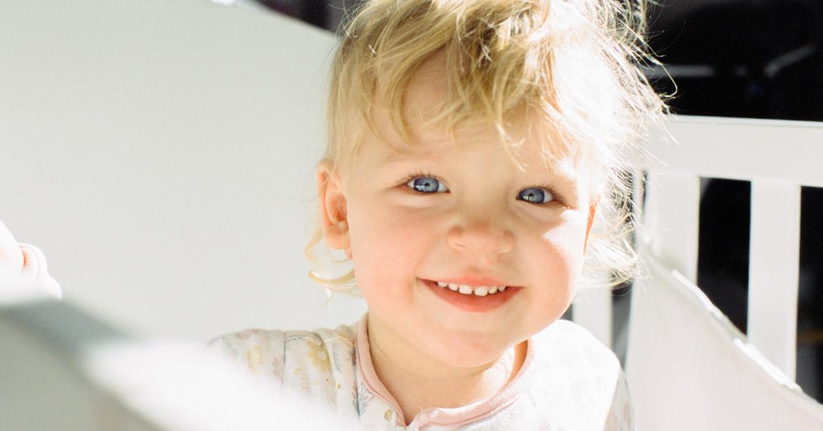 Bebé rubio sonriendo.