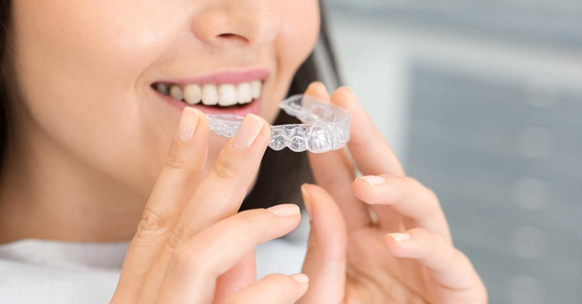 Mujer de cabello negro sosteniendo un alineador de Invisalign de los dientes superiores.