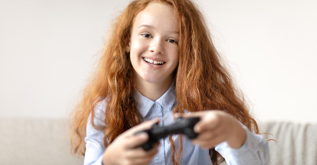 Niña pelirroja con los dientes incisivos separados sonriendo mientras juega con el mando de una consola.
