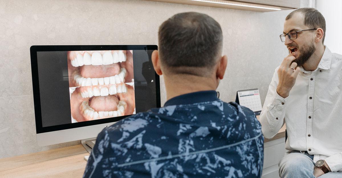 Dentista y paciente viendo el antes y después de una sonrisa en la pantalla de un ordenador.