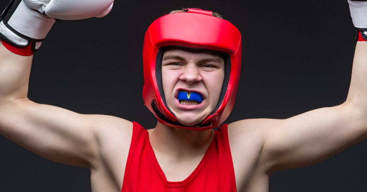 Luchador equipado con guantes, una camiseta de tiras roja, un casco rojo y un protector bucal azul.